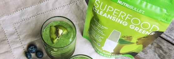 Glass of delicious NutriLiving smoothie next to Superfoods Super Greens